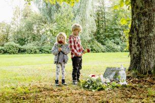 Pojke och flicka med blommor tar farväl av hund