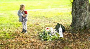 Flicka lägger rosor på gravplats hund