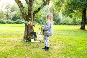 Flicka lägger rönnkvist på gravplats hund